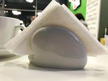 Suporte cerâmico de vidro branco, suporte para os guardanapo de papel para limpar na tabela em um café fotografia de stock royalty free