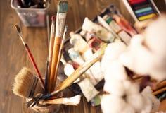Suporte com as escovas na tabela e nas pinturas na oficina do artista imagem de stock royalty free