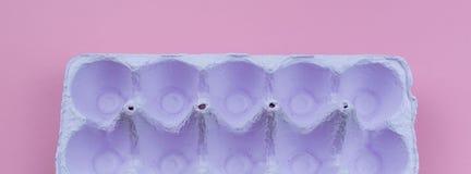 Suporte da bandeira para os ovos roxos em um fundo cor-de-rosa Imagens de Stock Royalty Free