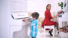 Suporte da criança perto do teclado de piano, fundo interior branco Conceito da educa??o do m?sico Os pais ricos apreciam a pater video estoque