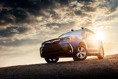 Suporte da guarda florestal de Subaru do carro na estrada do campo no por do sol Imagem de Stock Royalty Free