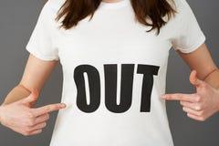 Suporte da jovem mulher que veste a camisa de T impressa com PARA FORA slogan Fotografia de Stock