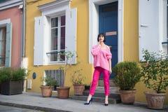 Suporte da mulher em sapatas do salto alto em Paris, france, férias Mulher na camiseta cor-de-rosa, calças na rua, forma Beleza,  foto de stock royalty free