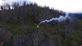 Suporte da mulher da vista aérea no penhasco com bomba de fumo filme