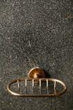 Suporte de bronze do sabão do vintage no muro de cimento cinzento com departamento raso do campo imagem de stock