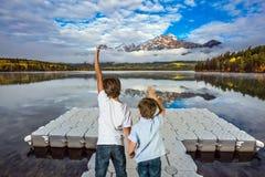 Suporte de dois meninos na doca plástica imagem de stock