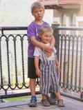 Suporte de dois rapazes pequenos que abraça no por do sol imagens de stock