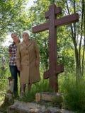 Suporte de duas mulheres ao lado de uma cruz de madeira Fotografia de Stock Royalty Free