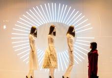 Suporte de exposição dos shopping na janela da menina no vermelho Imagem de Stock