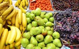 Suporte de fruto no mercado com as uvas e as cerejas das peras das bananas imagem de stock