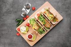 Suporte de madeira com os tacos de peixes saborosos Imagem de Stock