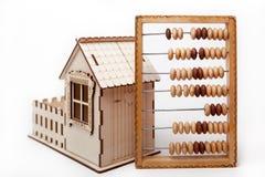Suporte de madeira do ábaco ao lado de uma casa pequena Imagens de Stock