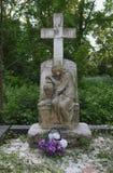 Suporte de pedra da estátua das lápides no cemitério velho monumento da escultura do túmulo à mãe do choro e da cruz fotografia de stock royalty free