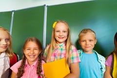 Suporte de quatro crianças com livros de texto junto Imagem de Stock Royalty Free