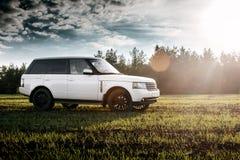 Suporte de Rover Range Rover da terra do carro no campo verde perto da floresta no por do sol Fotografia de Stock