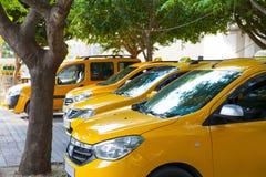 Suporte de táxis amarelo da cidade na máscara das árvores Imagem de Stock