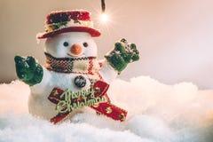 Suporte do boneco de neve entre a pilha da neve na noite silenciosa com uma ampola Fotos de Stock Royalty Free