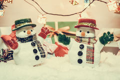 Suporte do boneco de neve entre a pilha da neve na noite silenciosa com uma ampola, Feliz Natal e noite do ano novo Imagem de Stock