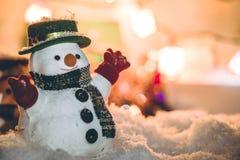 Suporte do boneco de neve entre a pilha da neve na noite silenciosa com uma ampola, Feliz Natal e noite do ano novo Imagem de Stock Royalty Free