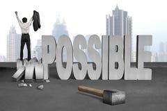 Suporte do bussinessman do elogio em esmagar a palavra impossível do concreto 3D Imagens de Stock Royalty Free