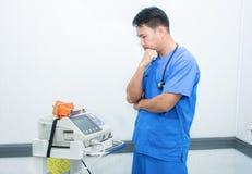 Suporte do doutor de Ásia perto do monitor e do estetoscópio do ECG Imagem de Stock