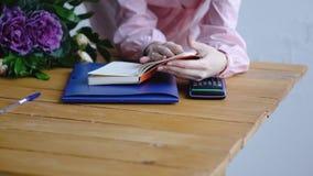 Suporte do florista atrás do contador e lido um caderno no florista imagens de stock royalty free