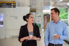 Suporte do homem de negócios e da mulher de negócios e riso, conversa sobre o negócio com caneca plástica disponível Imagens de Stock Royalty Free