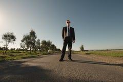 Suporte do homem de negócios na estrada Imagem de Stock