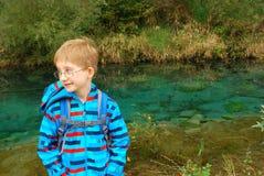 Suporte do menino por uma lagoa Fotos de Stock Royalty Free