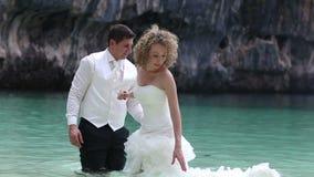 Suporte dos noivos na água pouco profunda na praia e no vestido posto na água vídeos de arquivo