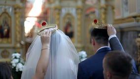 Suporte dos noivos na igreja no fundo de um iconostasis bonito Sacramento do casamento video estoque