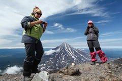 Suporte dos turistas das jovens mulheres da parte superior da montanha no fundo de c Imagens de Stock Royalty Free