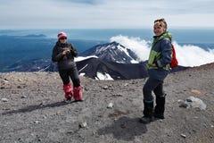 Suporte dos turistas das jovens mulheres da parte superior do vulcão ativo no Oceano Pacífico do backgroun Fotografia de Stock
