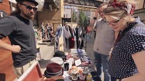 Suporte farpado do homem no contador da loja da rua com chapéus, luvas, cuba, bancos compradores Dia ensolarado do verão filme