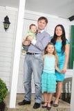 Suporte feliz da família de quatro pessoas no patamar da casa de campo nova. fotos de stock royalty free