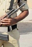 Suporte indiano do homem da polícia com a arma atrás da barricada na estrada foto de stock royalty free