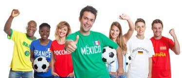 Suporte mexicano otimista do futebol com bola e fãs do othe imagem de stock royalty free