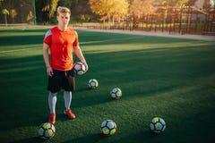 Suporte novo sério e concentrado do jogador de futebol no gramado e olhar na câmera Guarda uma bola à disposição Outros são fotografia de stock royalty free