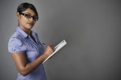Suporte seguro da mulher de negócio com prancheta Fotos de Stock