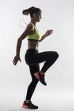 Suporte a silhueta iluminada do corredor fêmea na camiseta de alças amarela que faz o exercício alto dos joelhos foto de stock