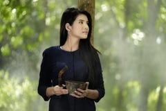 Suporte tailandês da mulher sob a árvore da borracha Fotografia de Stock Royalty Free