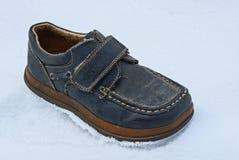 Suportes cinzentos e sujos velhos da bota na parte externa branca da neve imagem de stock