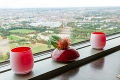 Suportes de Tealight e vaso de flor vermelhos na borda Fotos de Stock Royalty Free