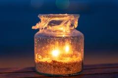 Suportes de velas de uma garrafa de vidro na tabela de madeira pela praia na noite foto de stock royalty free