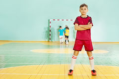 Suportes do jogador de futebol seguramente no salão de esportes Fotos de Stock Royalty Free