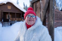 Suportes e sorrisos alegres da mulher felizmente na entrada da casa de madeira da vila fotos de stock royalty free
