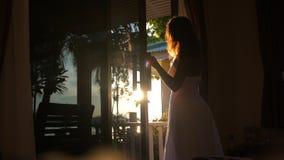 Suportes morenos bonitos da menina na entrada no amanhecer durante o nascer do sol com efeitos do alargamento da lente imagem de stock