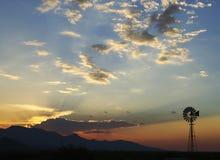 Suportes solitários de um moinho de vento mostrados em silhueta no por do sol Imagens de Stock Royalty Free
