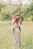 Suposição que Olhos de fechamento do noivo atrativo alegre de sua grinalda vestindo da menina bonita que está no jardim e que esp imagens de stock royalty free