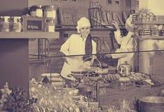 Suposición de ofrecimiento y bizcochos esponjosos del personal del café Foto de archivo libre de regalías